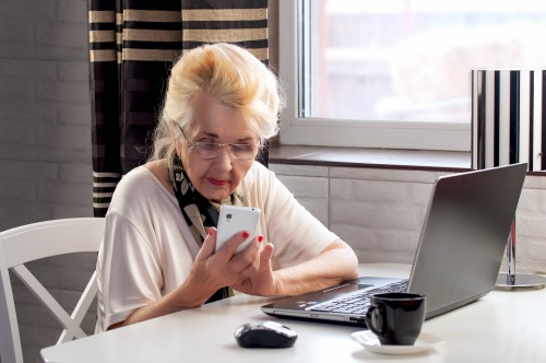 elderly lady talking on the phone and woking with computer